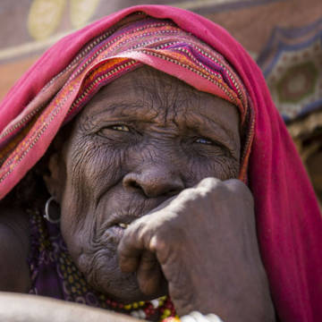 80 year old Teso from Marsabit in Kenya, wearing a pink shawl. She hasn't eaten for so long that she has to be given nutrient-rich liquid meals.