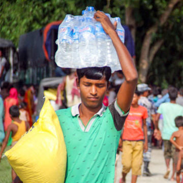 A man carries water and aid supplies